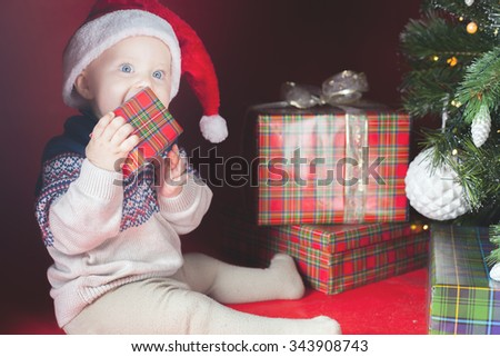 Happy surprised baby holding gift box or present at Christmas night, eve! Kid dressed in red Santa hat. Xmas and New Year holiday! Teething - stock photo