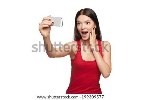 Happy surprised young girl taking pictures of herself through cellphone, over white background - stock photo