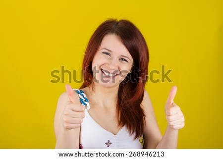 Happy surprised  young  woman very excited holding thumbs up isolated on yellow background. - stock photo