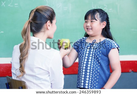 Happy teacher and asian elementary female student touching a green apple. - stock photo