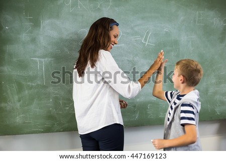 Happy teacher and school boy giving high five in classroom at school - stock photo