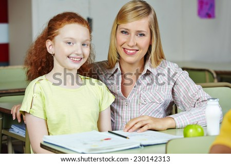 Happy teacher giving smiling girl private lessons after school - stock photo