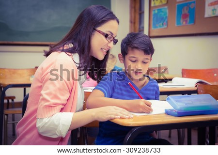 Happy teacher helping her students at the elementary school - stock photo