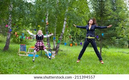 Happy teacher mother woman with schoolgirl kid jump outdoors - stock photo