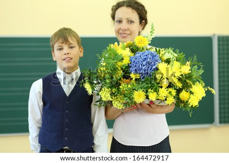 Happy teacher with big bunch of flowers and boy stand near chalkboard in classroom at school. Focus on boy. - stock photo