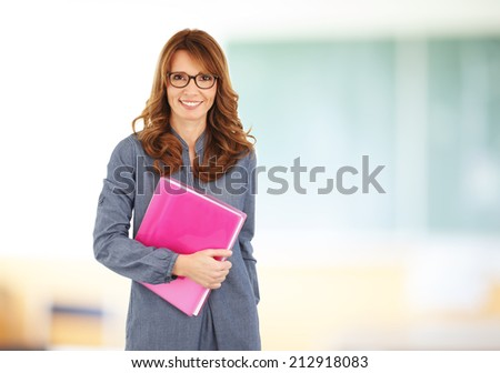 Happy teacher with notebook standing in front of black board at classroom. - stock photo