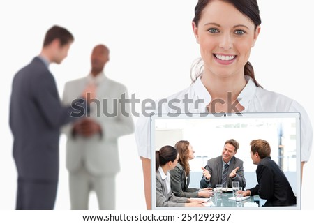 Happy team laughing together at a meeting against tradeswoman showing laptop with colleagues behind her - stock photo