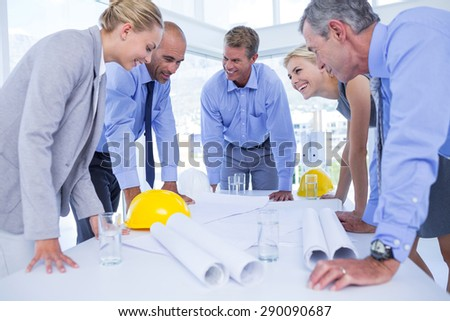 Happy team of business people speaking about construction plan in the office - stock photo
