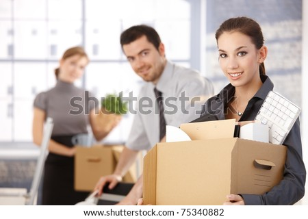 Happy team of businesspeople moving office, packing boxes, smiling.? - stock photo