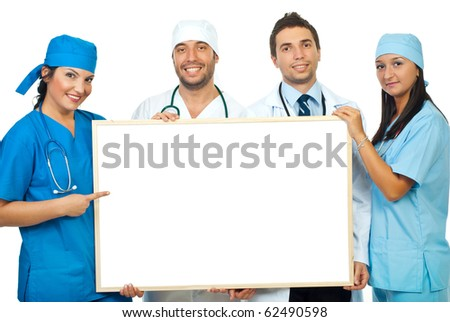 Happy team of four doctors holding a blank billboard and a doctor woman pointing to copy space of banner isolated on white background - stock photo