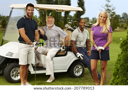 Happy team of golfers ready to play, standing and sitting around golf cart, smiling, looking at camera. - stock photo