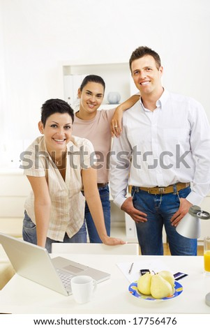 Happy team of office workers running small business, smiling. - stock photo