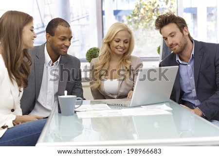 Happy team of young businesspeople working together, sitting around table, using laptop computer. - stock photo