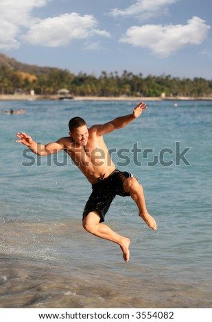 Happy teen boy jumping in the water - stock photo