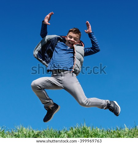 Happy teen boy jumping on grass hill against clear sky background - stock photo