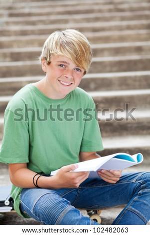 happy teen boy reading book - stock photo