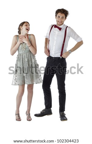 Happy teen couple dressed up in prom clothes stand together and laugh. Vertical, isolated on white, copy space. - stock photo