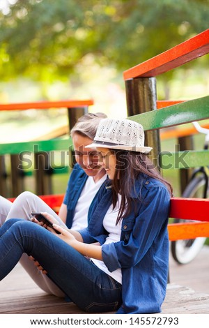 happy teen couple using tablet computer sitting on the bridge outdoors - stock photo