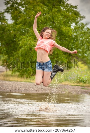 happy teen girl, jumps into a puddle  - stock photo