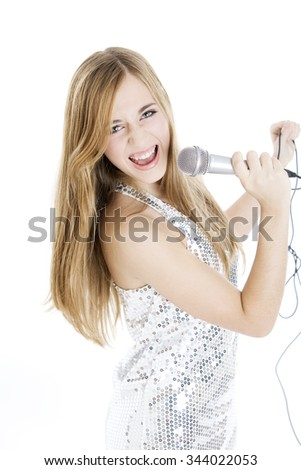 Happy teen girl singing with microphone - stock photo
