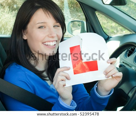 Happy teen girl sitting in her car tearing a L-sign after having her driver's licence - stock photo