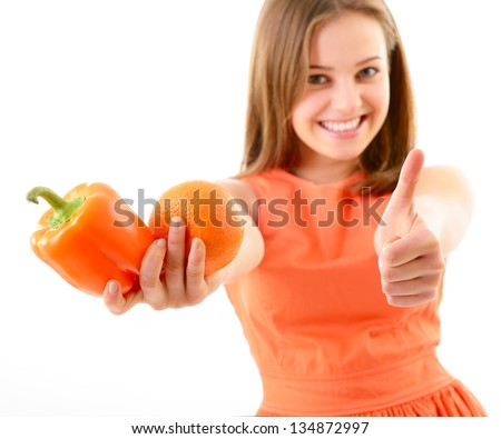 Happy teen girl thumb up holding and offering sweet pepper and mandarin like a healthy lifestyle, orange mood, diet and vegetarian concept, over white - stock photo