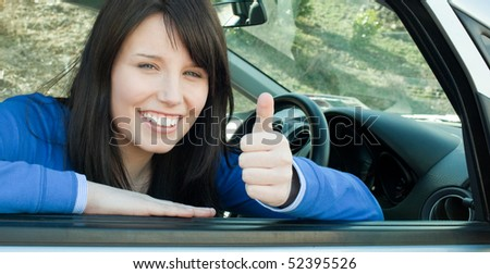 Happy teen girl with a thumb up sitting in her car after having her driver's licence - stock photo