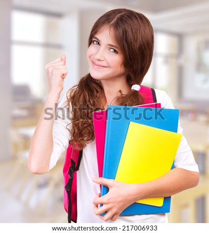 Happy teen girl with hand up in classroom, getting good mark, enjoying education at school, study and knowledge concept - stock photo