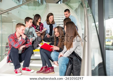 Happy teen girls and boys on the stairs school or college. Selective focus - stock photo