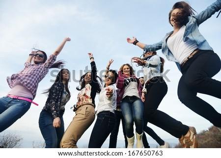 Happy teen girls having good fun time outdoors jumping on green meadow - stock photo