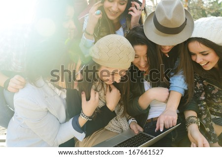 Happy teen girls having good fun time outdoors (with harsh sunlight effect) - stock photo