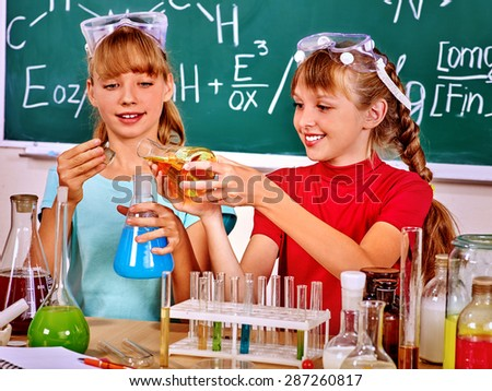Happy teen girls holding flask in chemistry class. - stock photo