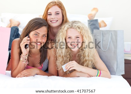 Happy teen girls lying on bed after shopping clothes - stock photo