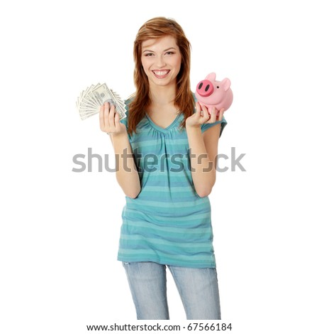 Happy teen holding a piggy bank and dollars, isolated on white background - stock photo
