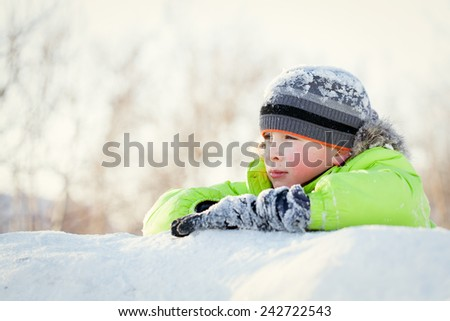 Happy teen in winterwear smiling while playing in snowdrift outside - stock photo