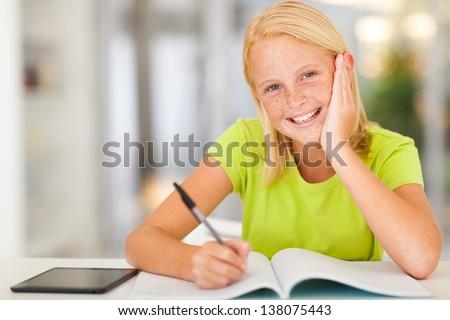 happy teen schoolgirl doing homework at home - stock photo