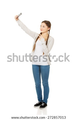 Happy teen woman taking selfies with smart phone. - stock photo