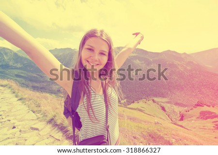 Happy teenage girl feel freedom in mountains scenery. Vintage instagram picture. - stock photo