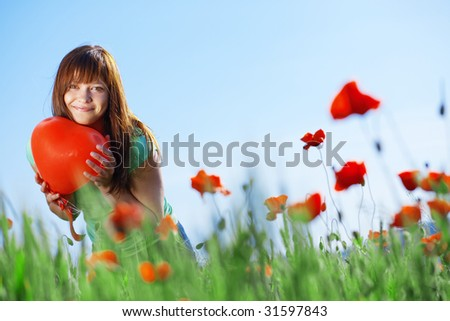 Happy teenage girl holding heart in poppies field - stock photo