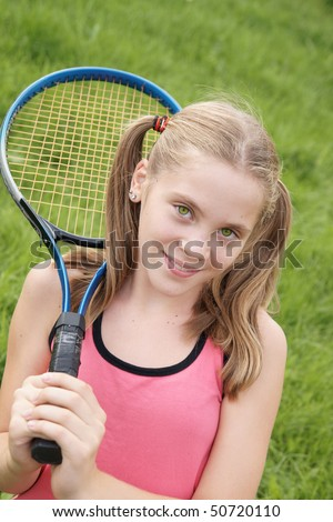 Happy teenage girl in sport outfits holding tennis racket on green grass background outdoors - stock photo