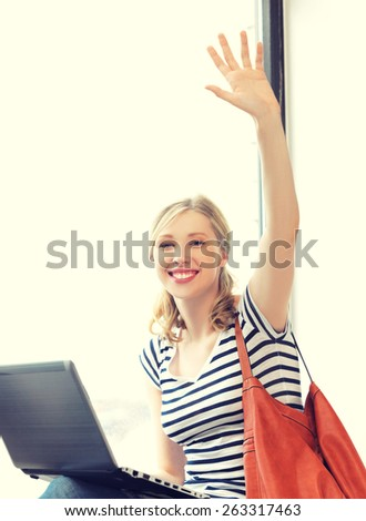 happy teenage girl waving a greeting with laptop - stock photo