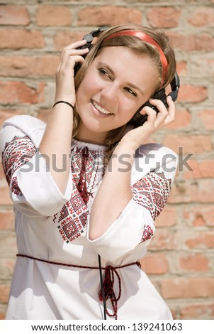 Happy teenage girl wearing traditional ukrainian blouse in headphones singing - stock photo