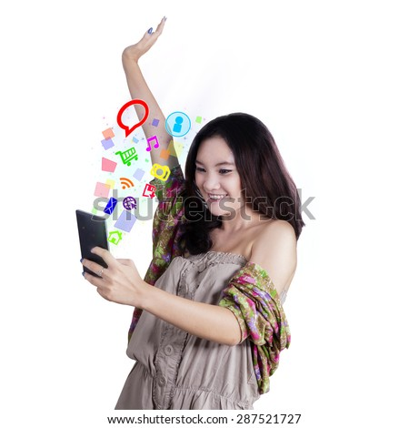 Happy teenage girl with casual clothes using cellphone to use social media, shot in the studio - stock photo