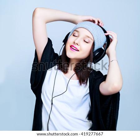 happy teenage girl with earphones, isolated against blue studio background - stock photo