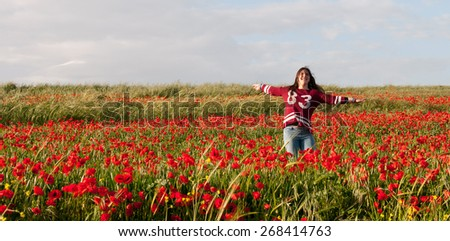 Happy Teenage Girl  with her hands on the air jumping in a red field of poppies full  of joy and happiness.  - stock photo
