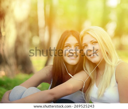 Happy teenage girls listening to music outdoors - stock photo