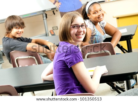 Happy teenage middle school or highschool students in class. - stock photo
