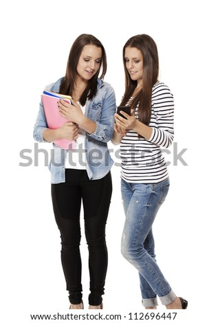 happy teenage students looking at a smartphone on white background - stock photo