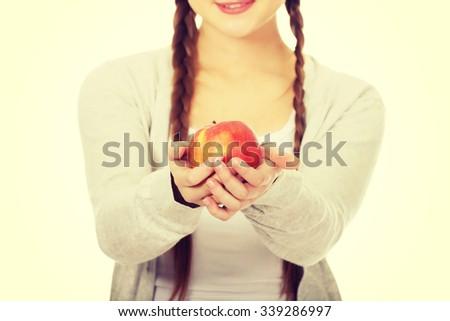 Happy teenage woman holding an apple. - stock photo