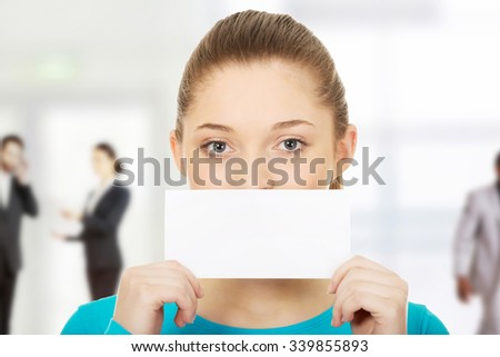 Happy teenage woman holding paper card. - stock photo